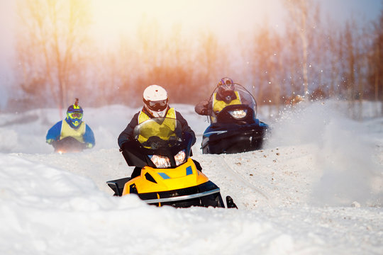 Snowmobile. Snowmobile races in snow. Concept team of friends chasing mountains.