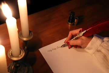 Woman's hand writes a letter with a quill in the candle light