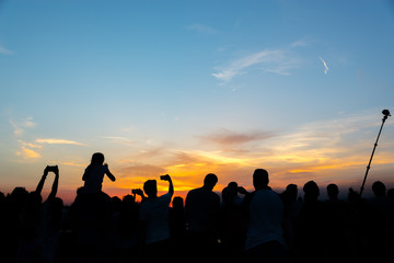 Crowd of people taking pictures of the sunset with mobile phones and selfie stick on a summer night in Florence, Italy