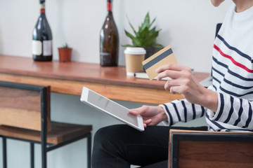 asian woman online shopping using credit card with tablet computer at cafe restaurant,Digital lifestyle concept,mobile banking,.
