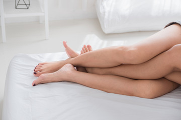 Close up barefoot legs of lesbian couple lovers sleep on white bed in bedroom at morning .