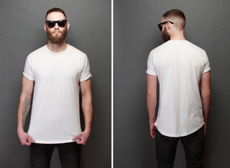Hipster handsome male model with beard wearing white blank t-shirt with space for your logo or design over gray background