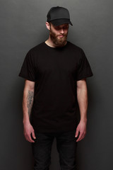 Hipster handsome male model with beard wearing black blank t-shirt and a black baseball cap with space for your logo or design in casual urban style