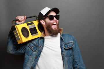Hipster man listening to cassette player and singing along