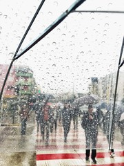 view from transparent umbrella with water drops to crowded city under rain and pedestrians with umbrellas