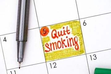 Reminder Quit Smoking in calendar with pen.