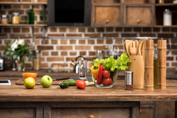 fresh organic fruits and vegetables, digital tablet and wooden kitchen utensils on table