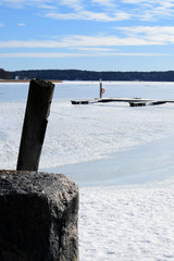 Winter seashore with frozen sea. Stone fence on foreground, empty boat dock on background. Vertical image with space for text.