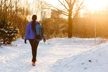 Image from back of walking sports woman with backpack in winter forest