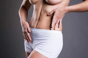 Slim woman in white panties on gray studio background, perfect female body