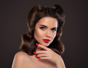 Red lips makeup and manicure nails. Retro Woman portrait. Beautiful brunette girl with pin up hairstyle over dark background. Presenting your jewelry product.