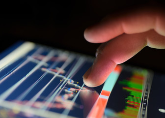 Traders finger using the touchscreen of a digital tablet displaying a financial market graph. close up
