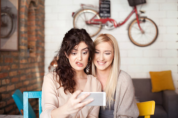 Two Female Friends In Cafe Taking Selfie Using Smart Phone. Making a face, having fun, laughing and enjoying their time