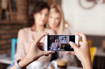 Close up of woman's hands taking a photo of girl friends with smart phone - Focus on the phone. Three woman having a coffee together and having fun.