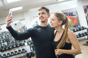 Young couple taking a selfie in gym