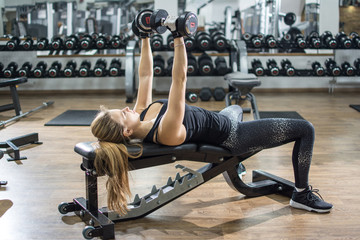 Fit girl lifting dumbbells while laying on weight bench at gym.