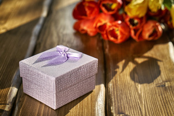 Gift box and flowers on the wooden table