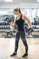 Full length of fit young woman lifting weighs in gym
