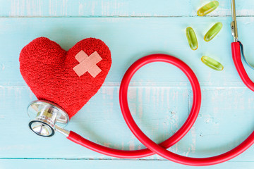 World health day, Healthcare and medical concept. Woman hand holding red heart with Stethoscope, notepad or notebook, thermometer and yellow Pill on Pastel white and blue wooden table background.