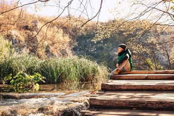 Boy sits on wooden bridge over the mountain lake