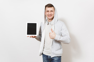 Young handsome man in t-shirt, light sweatshirt with hood, headphones holds tablet pc computer with blank screen for copy space, shows thumb up isolated on white background. Concept of technology