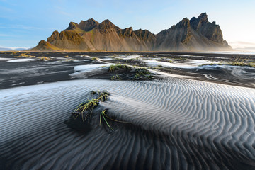 black sand with decorative hoarfrost at Stokksnes, Iceland with the mountain Vestrahorn in the background