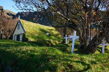the historic little church Hofskirkja in Iceland with cemetery and typical white crosses.