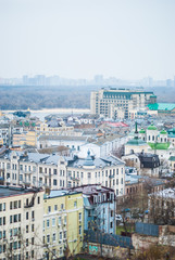 City of Kyiv (Kiev), capital of Ukraine, panorama. Colorful houses and Dnipro river on a background. Cloudy spring afternoon. Filtered.