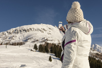 young woman with ski clothes take a picture of the mountain view with phone
