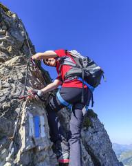 Junge klettert mit Klettersteig-Sicherung