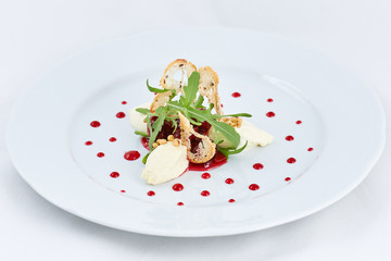 Delicious fresh dessert. White three pieces of ice-cream with strawberry and green leaves of arugula, and thin rusks in the centre of a plate with dots of strawberry jam.