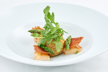 Delicious meal. Dish with pieces of grilled fish, rusks, green leaves of arugula and asparagus on a white plate.