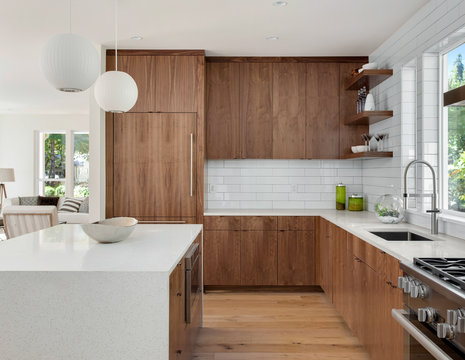 Modern Kitchen Interior in New Luxury Home with White Subway Tile, Oven and Range, Island, and Hardwood Cabinets and Floors