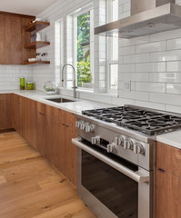 Kitchen Interior Detail in New Luxury Home with Oven and Range, Range Hood, Sink, and Subway Tile