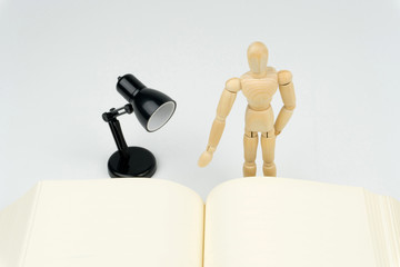reading concept : wood figure is reading a book with the black table lamp.