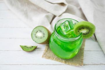 Green fruit juice with sliced kiwi on wood background