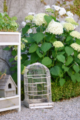 Country house atmosphere in a garden with gravel, white hydrangeas, birdhouses and white roses