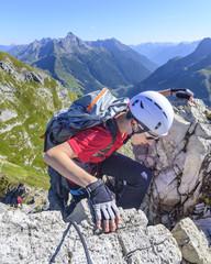 Teenager klettert im Klettersteig