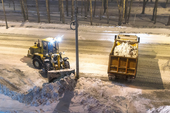 loader removes snow in the night