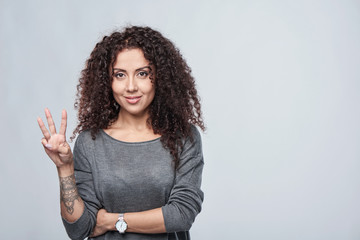 Hand counting - three fingers. Smiling woman showing three fingers
