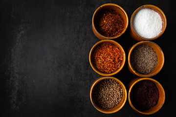 Set of spices on dark grey background.  Food art concept. Composition of bottles with colored herbs and spices.