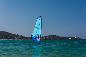 The men is wind surfing on the Corsica blue sea. Blue wind surf in foreground, Corsica nature in background.