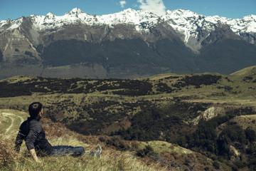Hombre joven disfrutando de las vistas de un paisaje con montañas evadas en Nueva Zelanda
