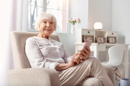 Advanced user. Cheerful senior woman sitting in an armchair and smiling at the camera while surfing the Internet on her phone