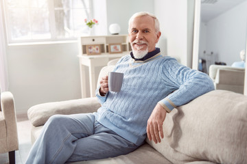 Favorite delicious drink. Upbeat senior bearded man sitting comfortably on the couch and posing for the camera while holding a cup of coffee