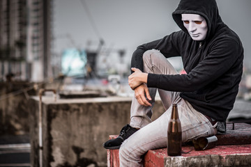 Mystery man in white mask with hoody jacket, sitting and hugs his knees up with broken empty bottle. depression self destruction and alcoholism. Major depressive disorder concept