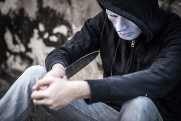 Mystery man in the white mask trying to kill himself considering suicide with knife, depression self destruction suicidal addiction massive depressive disorder concept Wall mural