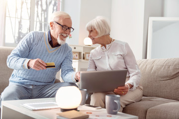 We are shopaholics. Upbeat elderly couple shopping online together and the man pointing at the laptop, choosing the item to buy, while giving his bank card to pay for it