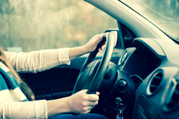 Young woman riding a car, hands on the steering wheel / driving-wheel (color toned image)