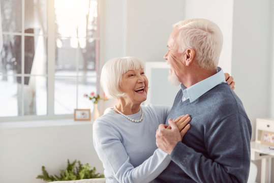 Loving couple. Joyful elderly husband and wife dancing in the living room while smiling at each other widely